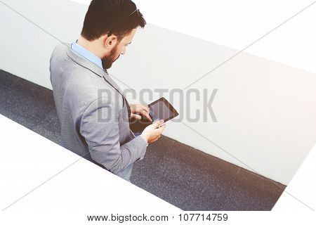 View from above of young purposeful male lawyer dressed in formal wear work on touch pad during brea