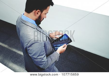 Young male skilled manager in luxury suit using digital tablet in modern office