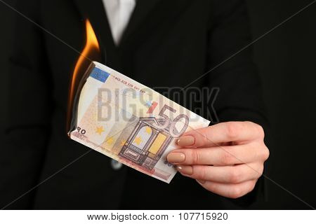 Woman burning Euro banknotes closeup