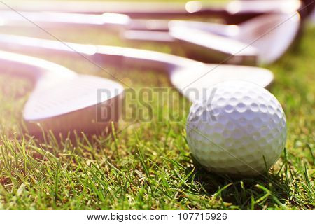 Different golf clubs in a row and balls on a green grass, close up