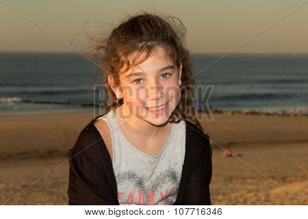 Caucasian Pre-teen Girl On Beach Looking At Viewer