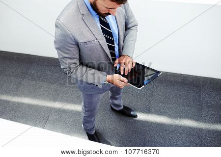 Top view of young purposeful smart male lawyer dressed in formal wear working on touch pad during br