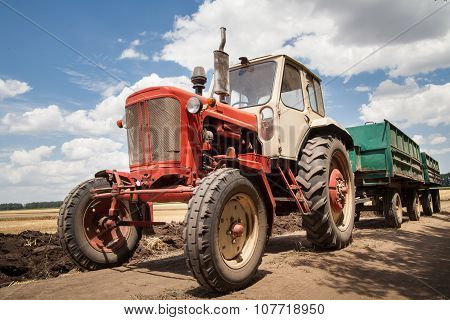 Old Tractor In Field, Against A Cloudy Sky