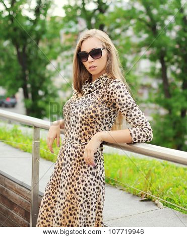 Beautiful Blonde Woman Wearing A Leopard Dress And Sunglasses In City