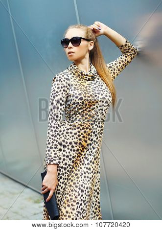Fashion Beautiful Blonde Woman Wearing A Leopard Dress And Sunglasses With Handbag Clutch In The Cit