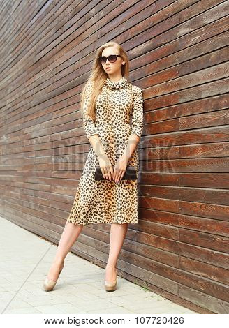 Fashion Beautiful Woman Wearing A Leopard Dress And Sunglasses With Handbag Clutch In The City