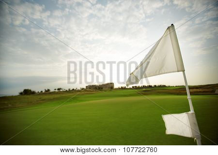 Green Field And Flag On The Golf Course