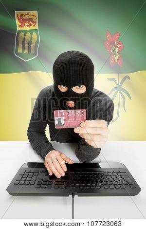 Hacker With Canadian Province Flag On Background Holding Id Card In Hand - Saskatchewan