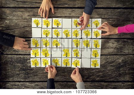 Top View Of A Group Of Many Scientists Each Holding A Card With A Yellow Light Bulb