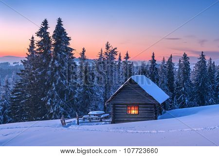 Fantastic landscape glowing by sunlight. Dramatic wintry scene with snowy house. Carpathians, Ukraine, Europe.