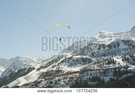 Paraglider Flying Over A Mountain Valley