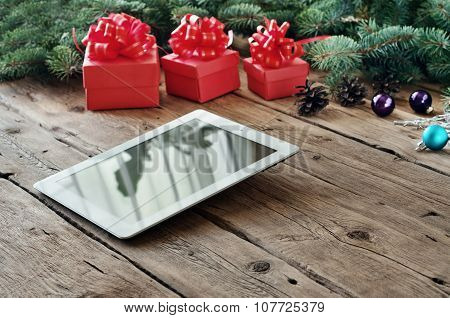 Tablet Computer With Christmas Gifts On Wooden Table Closeup