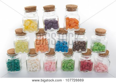 Clear Glass Jar Of Candy And Colorful Jelly Beans Spilled From Jar