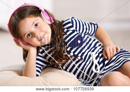 Little girl in striped dress with pink headphones in the room