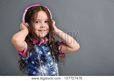 Beautiful little girl listen music with pink headphones on grey background