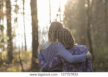 Two Girlfriends Or A Lesbian Couple Standing In Autumn Woods Leaning On Each Other