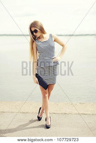 Beautiful Young Woman Wearing A Striped Dress, Sunglasses And Handbag Clutch On Sea