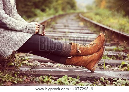 Young woman sitting on rail track