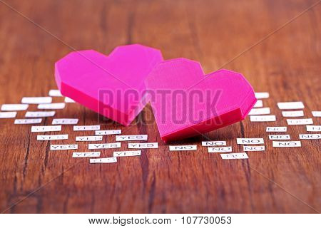 Two pink hearts with yes and no on wooden background