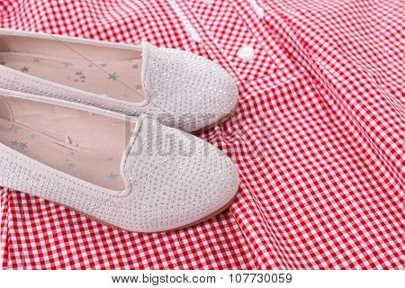 Shiny pink shoes on red plaid shirt background, close up