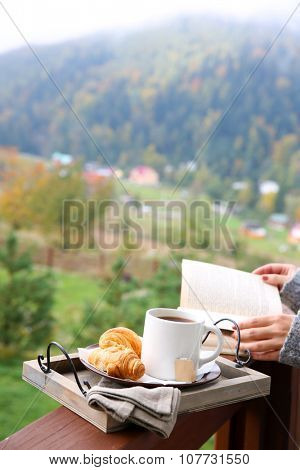 Wooden tray with light breakfast at terrace on mountains background