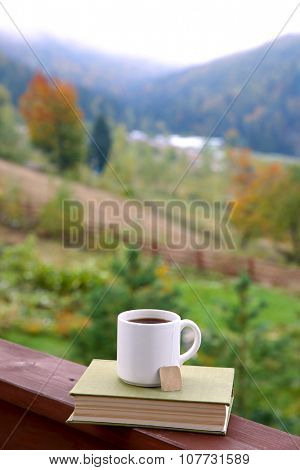 Tea and book on balcony fence, on mountains background
