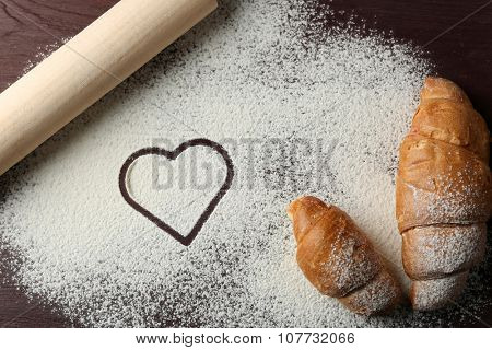Heart of flour, croissants and rolling pin on table background