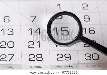 Black Magnifying Glass Over Calendar