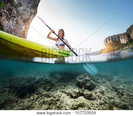 Split shot of the lady paddling the kayak in the calm tropical sea with underwater view of the bottom