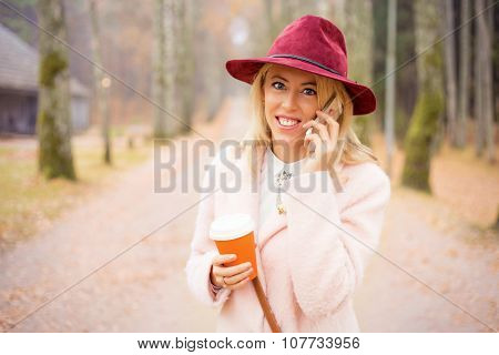 Woman in red hat talking on the phone and holding coffee cup