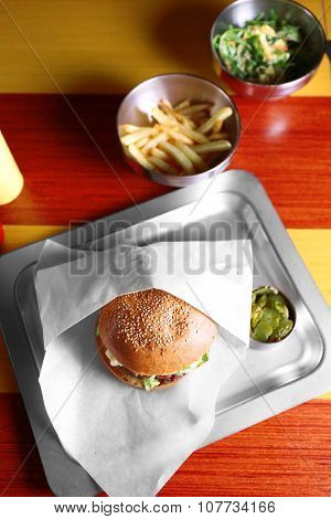 Sandwich and tinned cucumbers on a metal tray closeup