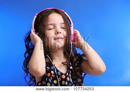 Happy little girl in colourful shirt with pink headphones on blue background