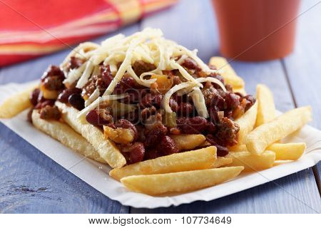 Chili con carne and French fries on a paper plate