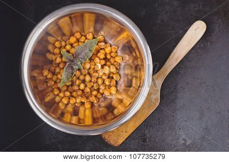 Chickpeas Baked With Spices In Metal Bowl And Wooden Spatula On Black Surface With Place For Text