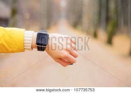 Woman looking at smartwatch while having a walk