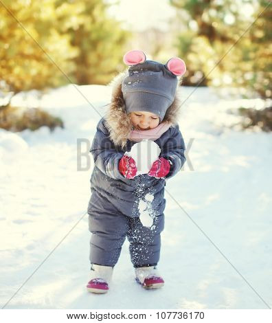 Little Child Playing With Snowball In Winter Day