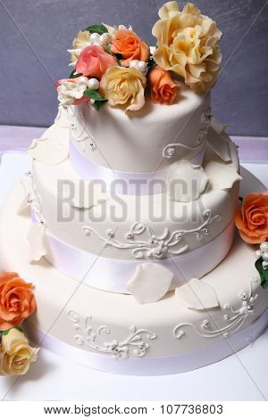 White wedding cake decorated with flowers on grey background