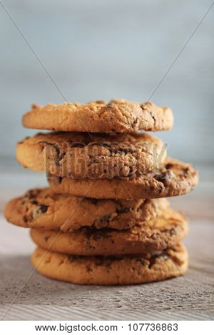 Close up focus view on cookies with chocolate crumbs on wooden table against blurred blue background