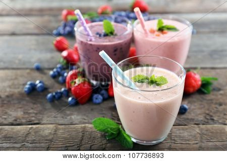 Tasty blueberry, strawberry and milk yogurts in a row decorated with berries and mint on wooden background, close up