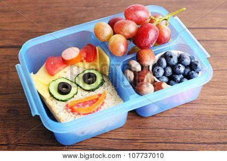 Creative sandwich with fruits and nuts in lunchbox on wooden background