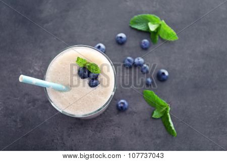 Tasty yogurt decorated with blueberries and mint on grey background