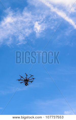Black Drone In The Sky. Bright Picture Of Quadcopter Flying And Making Photos And Video From High..