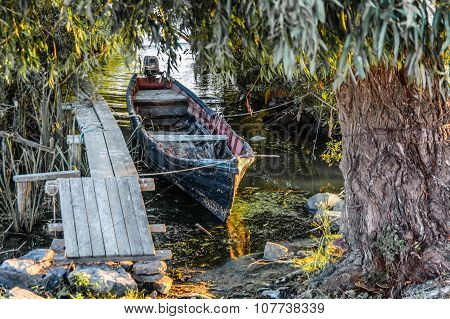Old Boat On The Dock Among The Trees. Rustic Landscape With Wooden Pier In The Summer Sunset..