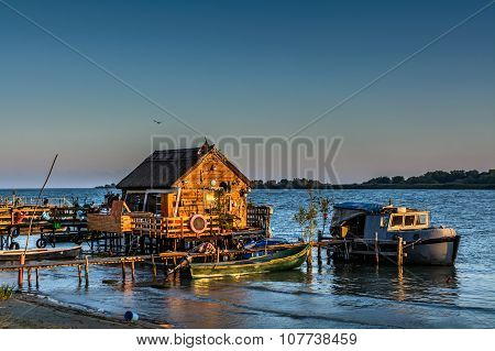 Fisherman's House, The Old Dock And The Boat On The Lake. Rustic Landscape With Wooden Pier In The S