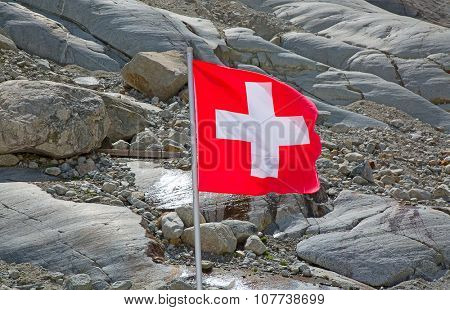 Swiss flag against rocky mountains