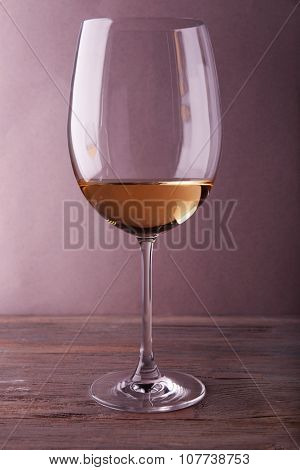 Glass of white wine on wooden table