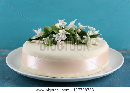 Cake with sugar paste flowers on color wooden background