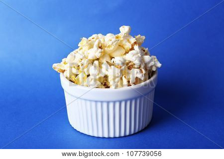 Salted popcorn on blue background