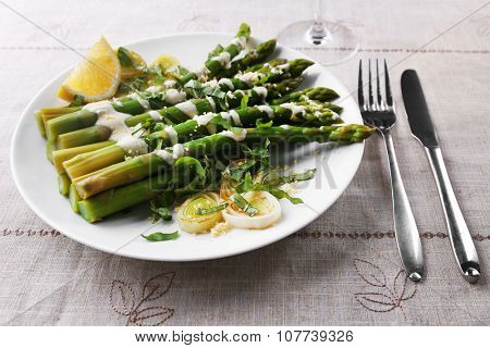 Appetizing asparagus in sour cream sauce with onion, cheese and lemon on the table, close up