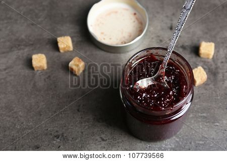A jar of tasty jam, a spoon and crackers on grey background